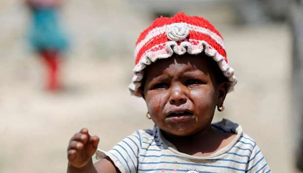 File photo shows a girl crying as she waits with relatives to receive food aid from the local charit