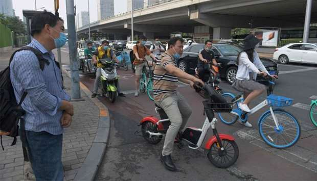 People wear masks as they wait at an intersection in Beijing