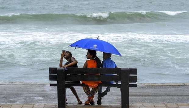 Children take shelter under an umbrella as they sit on a bench facing the sea along the coast during