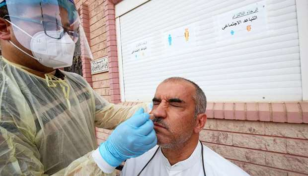 A Kuwait health ministry worker conducts a random test for the novel coronavirus (Covid-19) in Kuwai