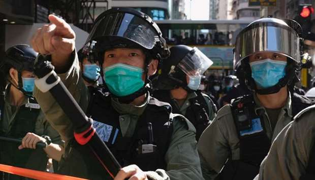 Riot police ask people to leave to avoid mass gathering during a protest against the looming nationa