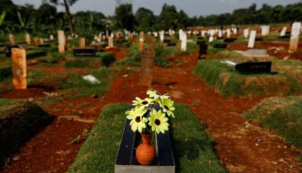 A pot of artificial flowers is placed on a grave at a burial area provided by the government for vic