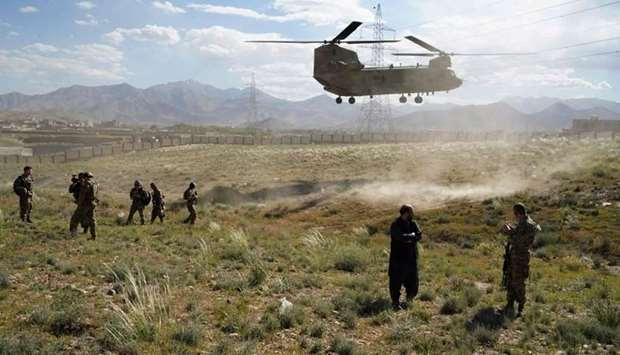 A US military Chinook helicopter lands on a field outside the governor's palace during a visit by th