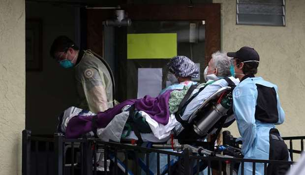 MEDICAL EMERGENCY: Emergency medical technicians move a patient on a gurney from an ambulance into t