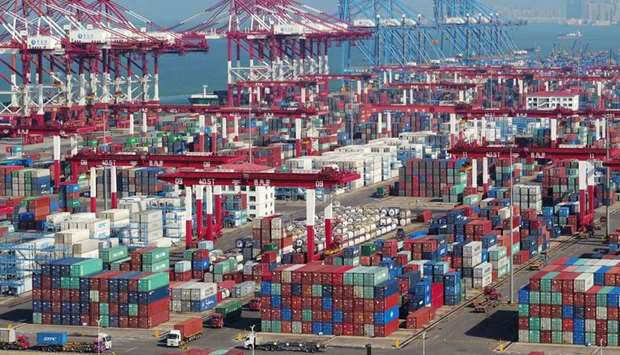 FILE PHOTO: Containers and trucks are seen at a terminal of the Qingdao port in Shandong province, C