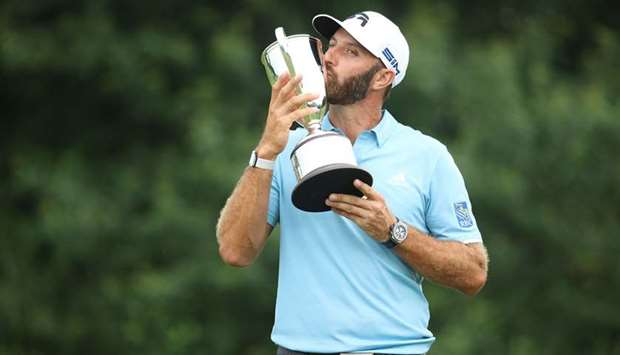 Dustin Johnson of the United States poses with the trophy after winning the Travelers Championship a