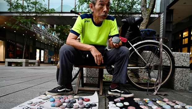 """Artist Wu Rong-bi, also as know as """"Uncle Stone"""", displaying colourfully painted stones along a stre"""