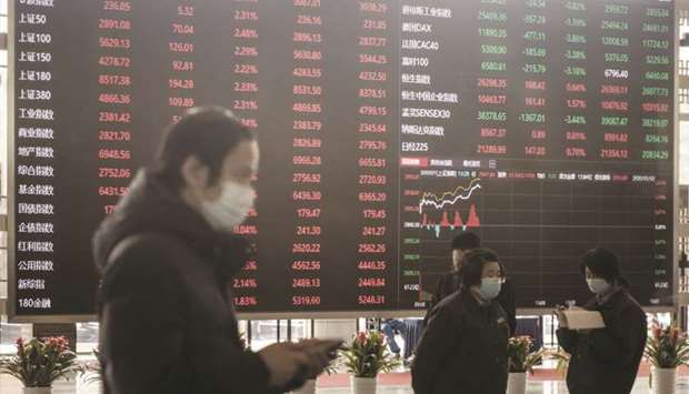Employees and visitors wearing protective masks walk past an electronic stock board at the Shanghai