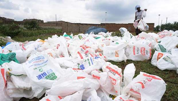 File photo shows a woman sorting out plastic bags after washing them for reuse at the shores of a ri