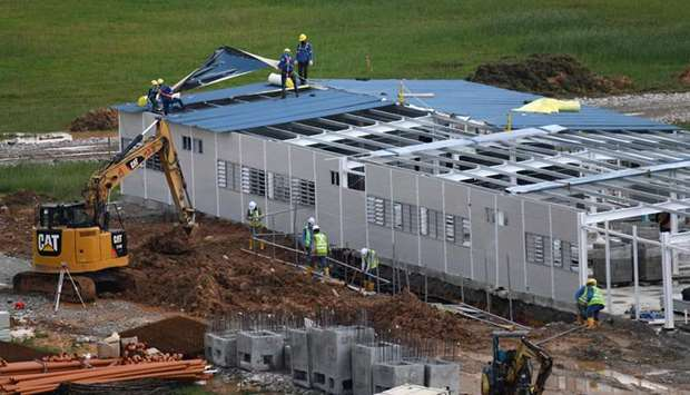 Workers construct a new quick-build dormitory for foreign workers in Singapore yesterday as the nati
