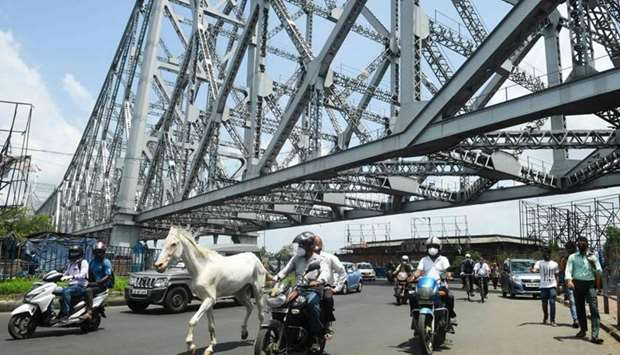 A horse rides through traffic along the Howrah Bridge after the government eased a nationwide lockdo