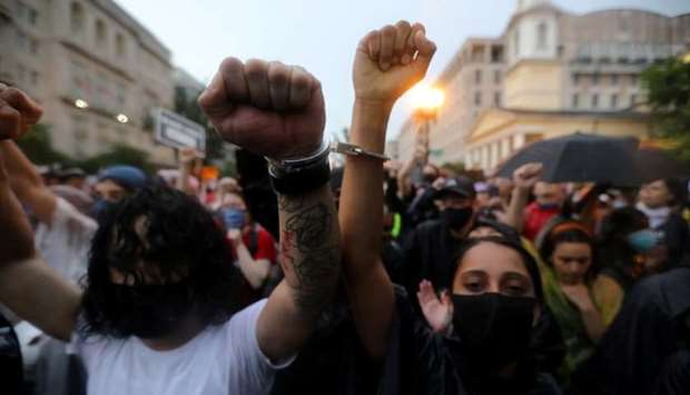 Protesters handcuff their wrists as they march the streets, as protests against the death in Minneap
