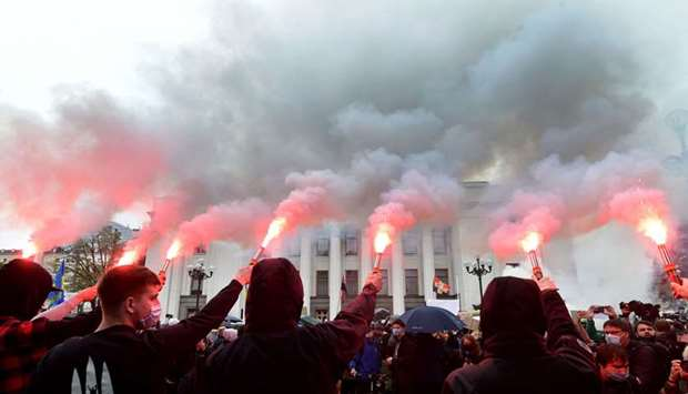 Demonstrators burn flares outside the Ukrainian parliament in Kyiv during a demonstration calling fo