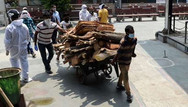 Workers pull a cart loaded with cremation wood at the Nigambodh Ghat cremation ground in New Delhi o