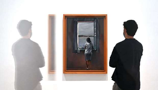 A man stands next to the painting Girl at the window by Spanish painter Salvador Dali at Madrid's Re