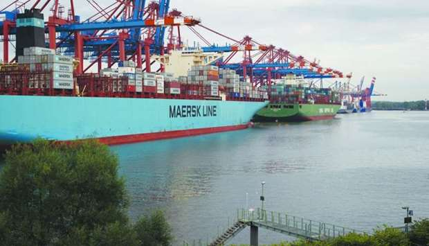 Shipping containers sit on a cargo vessel operated by AP Moeller-Maersk (left) on the dockside at th