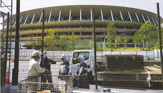 Workers install additional security fence outside Olympic Stadium for the Olympic Games in Tokyo, Ja