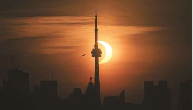The sun rises behind the skyline during an annular eclipse yesterday in Toronto, Canada.