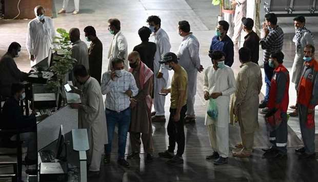 People stand in a queue to register to receive a dose of the Covid-19 coronavirus Sinopharm vaccine