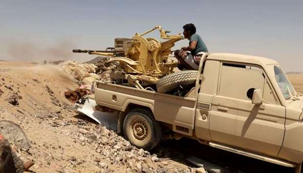 A Yemeni government fighter fires a vehicle-mounted weapon at a frontline position during fighting a