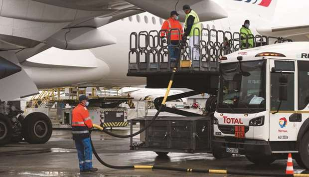 Workers connect a tanker truck to an Airbus A350 passenger plane, operated by Air France-KLM, during