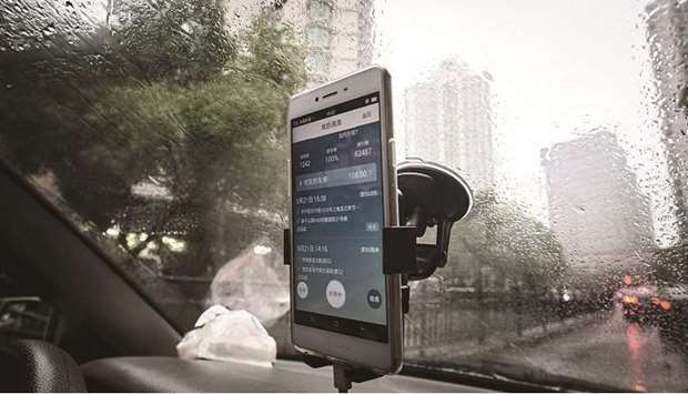 The Didi Chuxing application is displayed on a smartphone screen onboard a vehicle in Shanghai. The