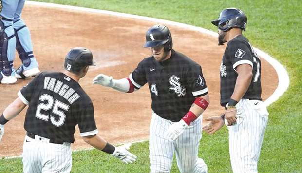 Chicago White Sox catcher Yasmani Grandal (centre) is greeted by teammates Andrew Vaughn (left) and