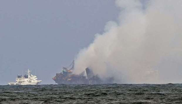 An Indian Coast Guard ship (L) tries to douse off the fire as smoke billows from the Singapore-regis