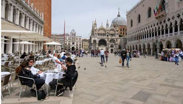 People sit at outdoor tables at St. Mark's Square as Italy lifts quarantine restrictions for travell