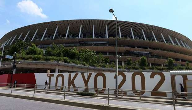 People walk outside the Olympic Stadium (National Stadium) built for Tokyo Olympic Games