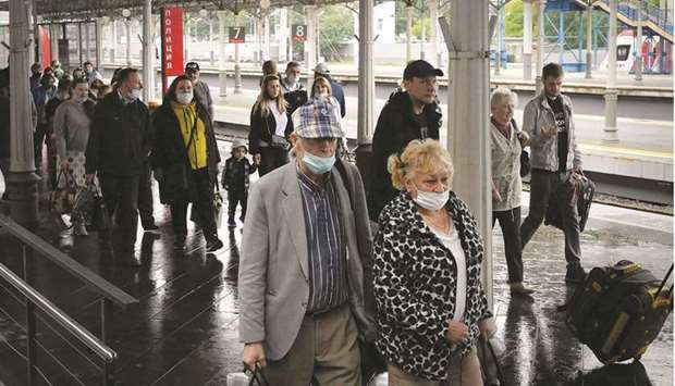 Passengers, mostly unmasked and with some wearing face masks improperly, are seen yesterday on a pla