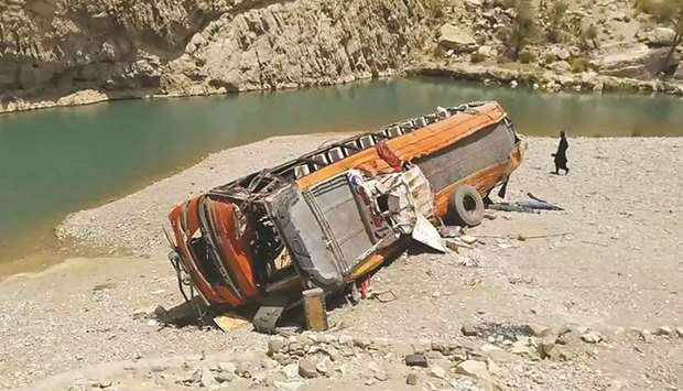 A man walks past a damaged bus in a remote district of Balochistan. The bus carrying dozens of pilgr