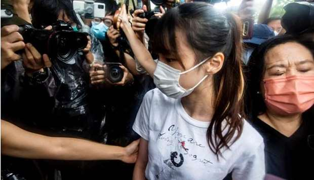 Hong Kong pro-democracy activist Agnes Chow (C) walks through the media pack after being released fr