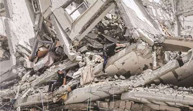 Palestinian workers clear the rubble and debris in Gaza City's Al-Rimal neighbourhood, which was tar