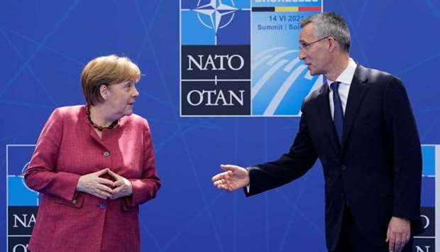 German Chancellor Angela Merkel speaks with Nato Secretary General Jens Stoltenberg as they pose for