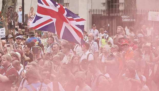 Protesters fly a Union flag as a smoke bomb goes off at a gathering outside Downing Street as they d