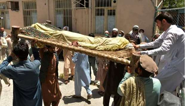 Relatives carry the body of a polio worker who was shot dead by gunmen in a string of targeted attac