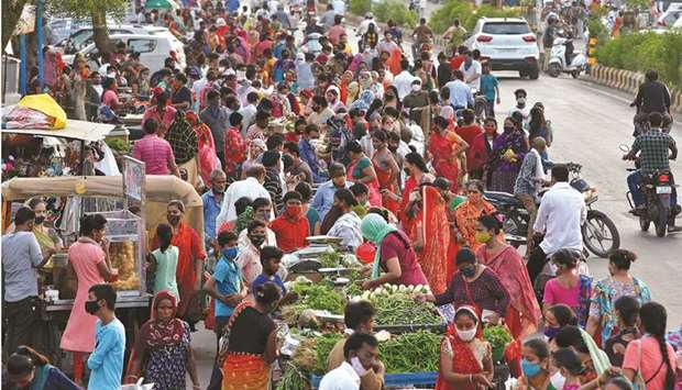 People shop at a crowded roadside vegetable market after authorities eased coronavirus restrictions,