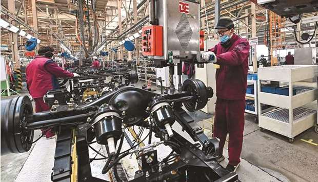 Employees work on a truck assembly line at a factory for the vehicle manufacturing company Jianghuai