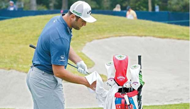 Jon Rahm cleans his club in the practice area during a practice round of the US Open at Torrey Pines