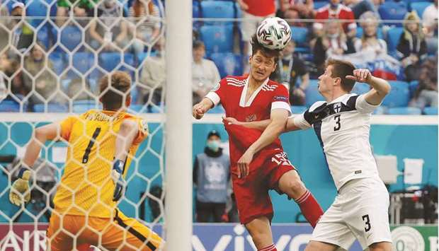Russia's forward Aleksey Miranchuk (centre) vies for the ball with Finland's defender Daniel O'Shaug