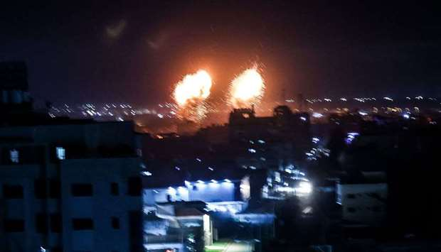 Explosions light-up the night sky above buildings in Gaza City as Israeli forces shell the Palestini
