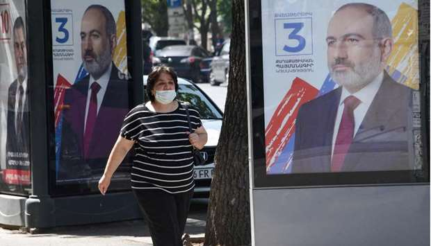 A woman wearing a face mask walks past campaign banners of acting Prime Minister Nikol Pashinian in