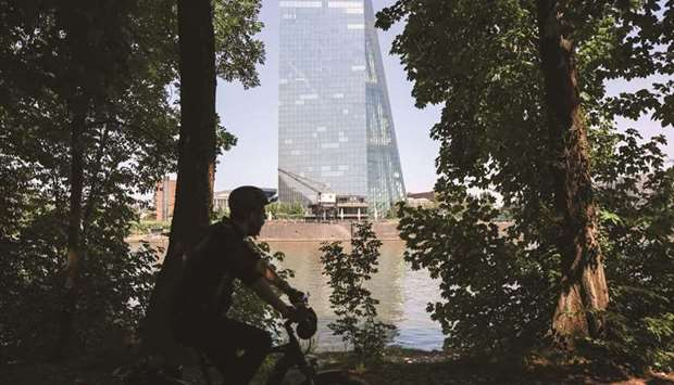 A cyclist rides past the European Central Bank (ECB) headquarters beside the River Main in Frankfurt