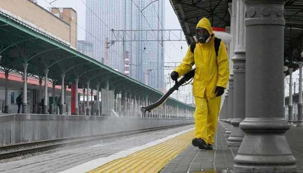 A specialist wearing personal protective equipment (PPE) sprays disinfectant while sanitizing the Ri