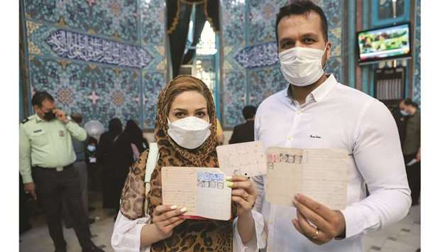 An Iranian couple holds documents after voting during presidential elections at a polling station in