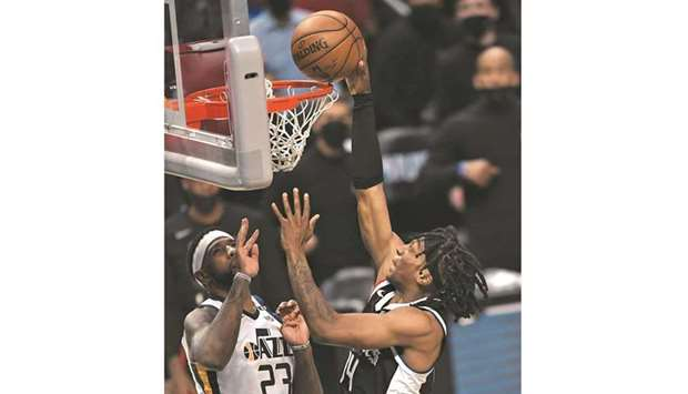 Terance Mann of the Los Angeles Clippers scores a basket against Royce O'Neale of the Utah Jazz duri