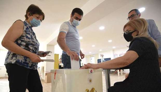 Voters cast their ballots at a polling station during early parliamentary elections in Yerevan