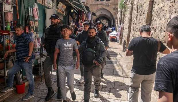 Members of the Israeli security forces detain a Palestinian youth in Jerusalem's Old City on June 18