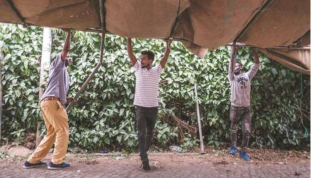 Workers set up a tent, that will be used as a polling station in the upcoming elections tomorrow, in